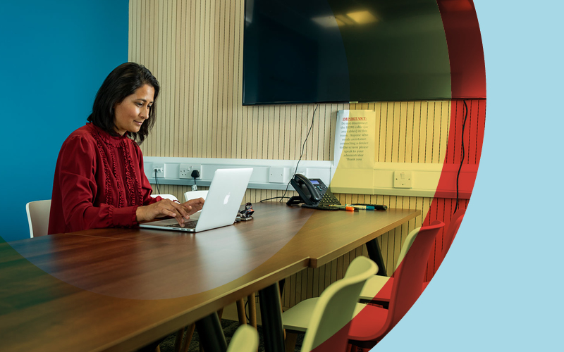 Woman at long desk working on a laptop