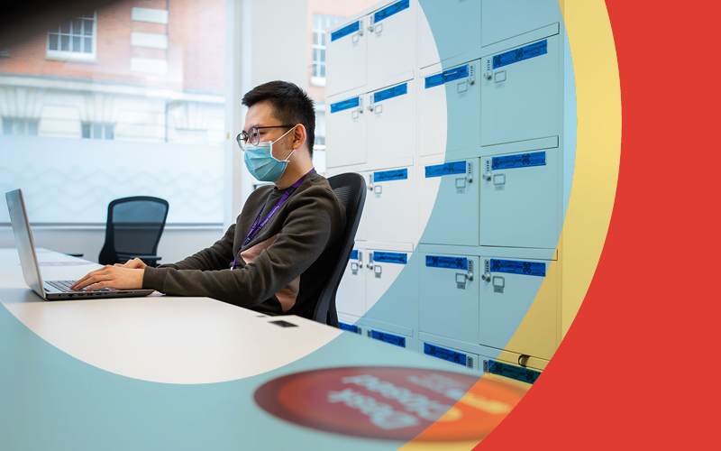 Man in face mask working at a desk
