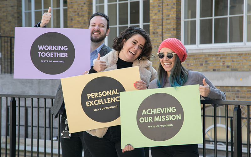 UCL Ways of Working group of three people holding supporting indicators signs