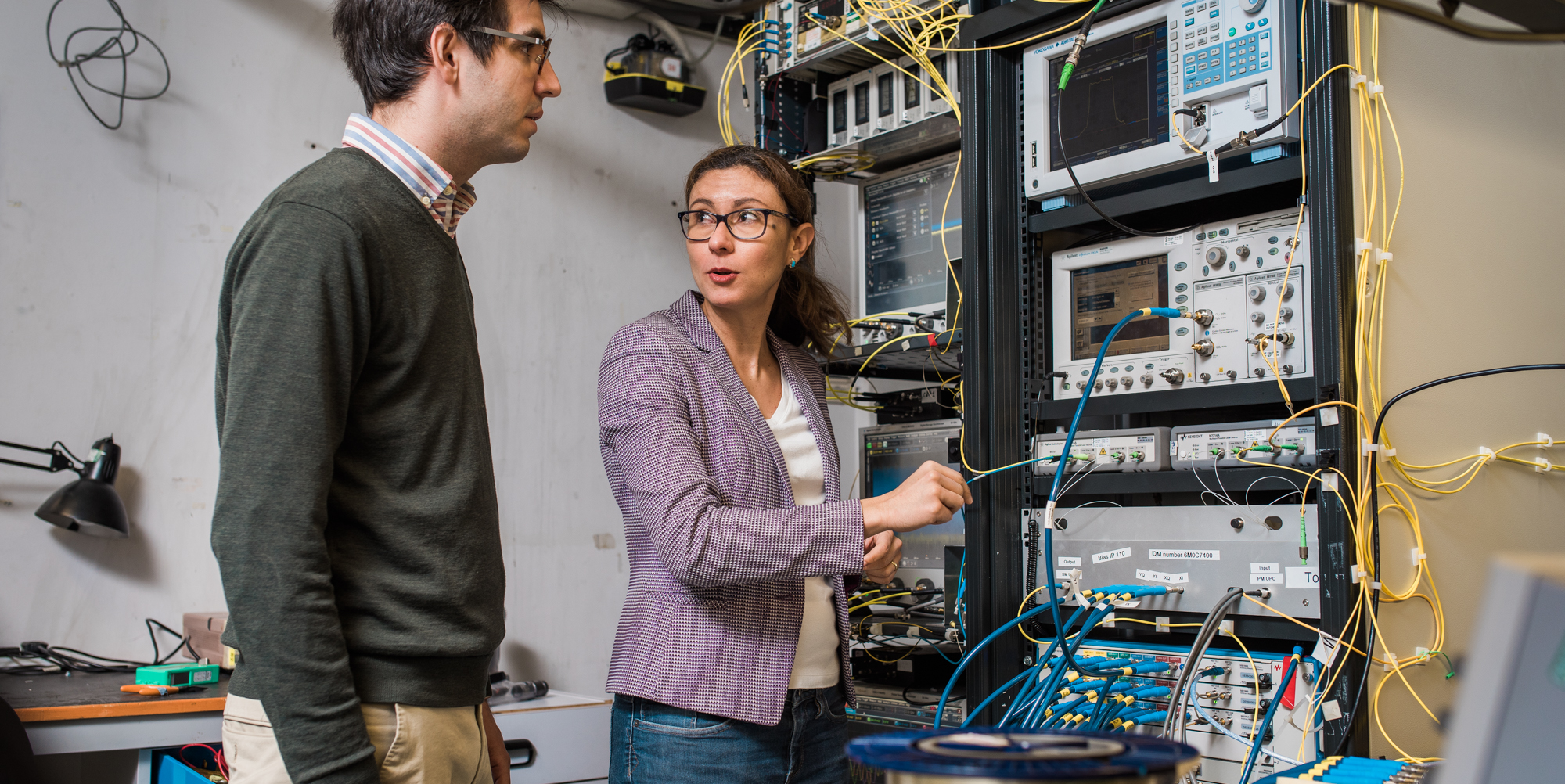 Two researchers in front of a rack of experimental equipment with optical fibres