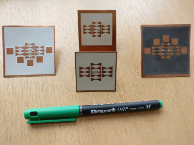 Several photographs of antenna designs, next to a pen for scale, the antenna arrays are approximately 1/4 the length of the pen.