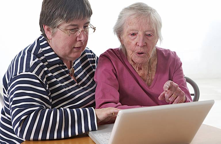 Elderly woman getting help with a computer