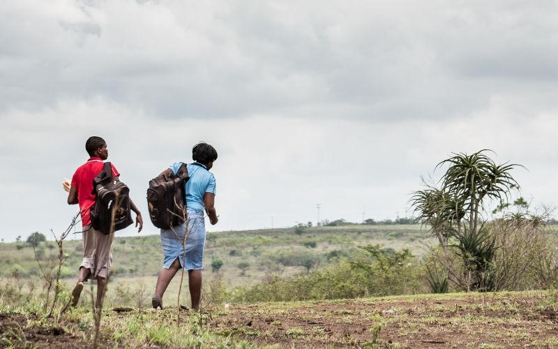 Two people walking in field