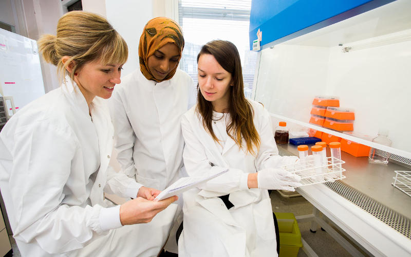 Three female scientists looking at document in lab