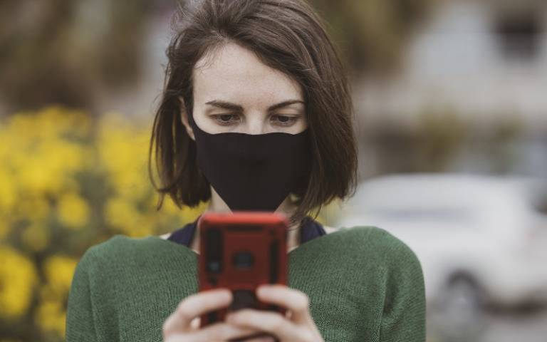 Woman wearing mask whilst using mobile phone