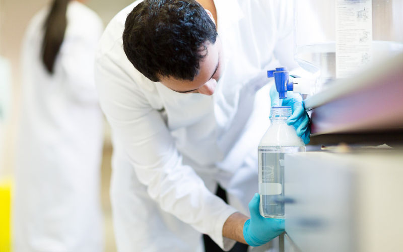 Image shows researcher in laboartory pouring liquid in to flask