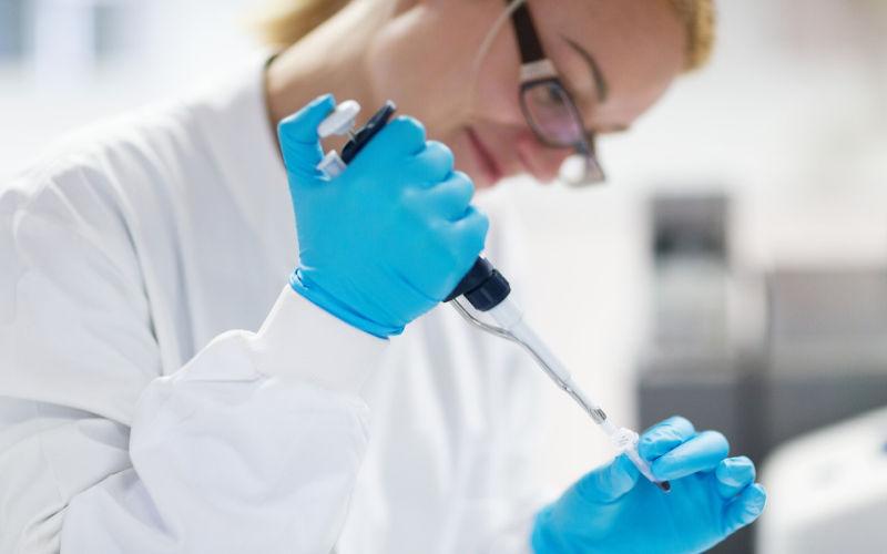 Female researcher pipetting liquid in to a PCR tube