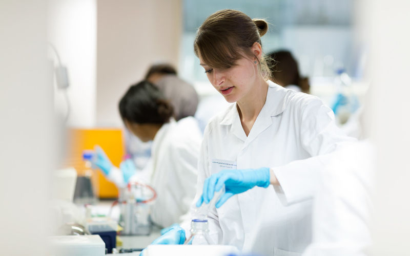 Students in the laboratory: close up of female student pouring liquid in to flask