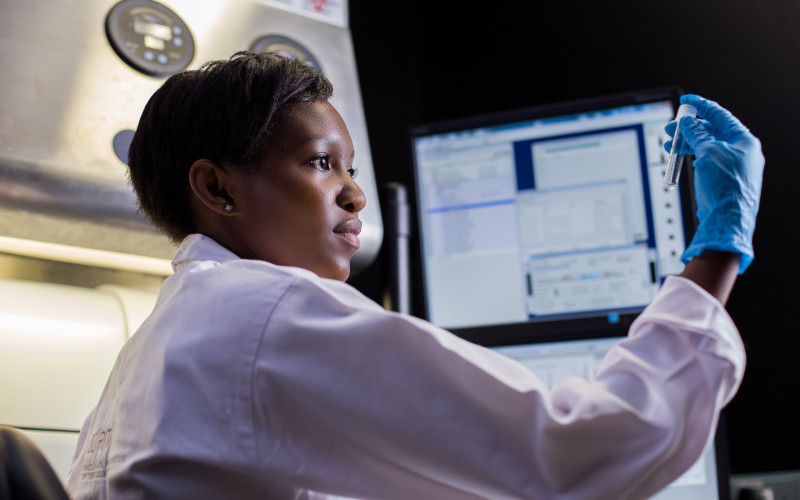 Female Africa Health Research Institute (AHRI) researcher holding a test tube in a laboratory with computer screen showing in the background