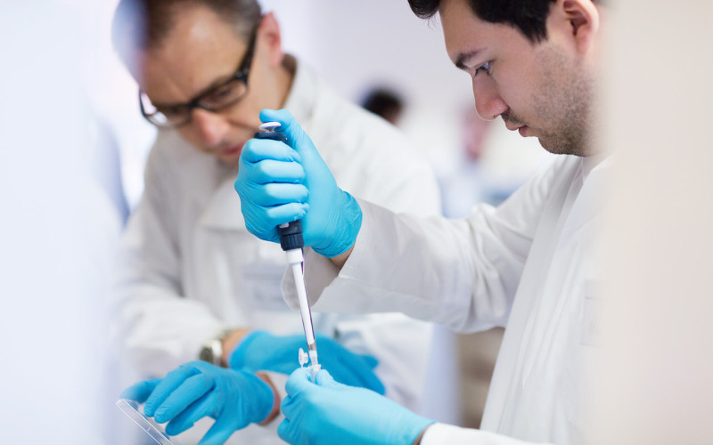 Male researchers working in laboratory, with one using a pipette