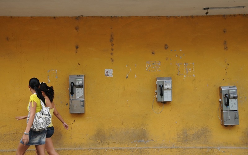 Two women walking past a yellow wall, GFRN people page image