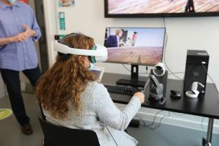 wide area haptics - a women uses a VR headset and haptics to collaborate on a simulated task