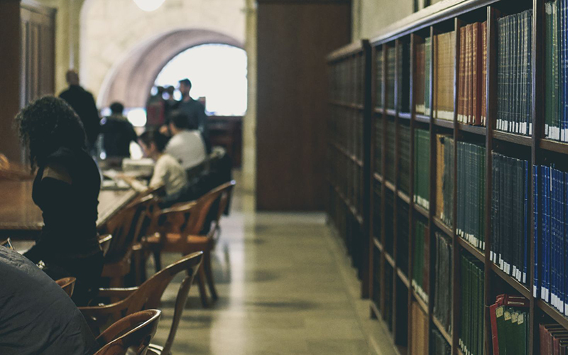 Library with books and students. Image: Davide CantellionUnsplash