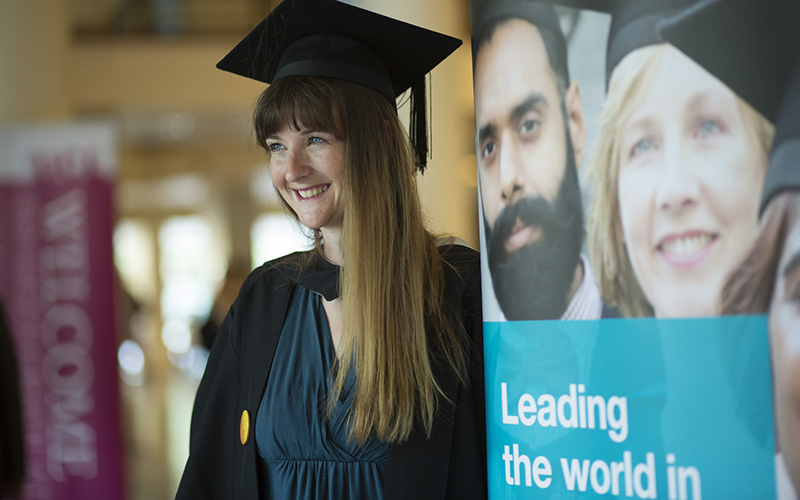 Graduate next to IOE banner
