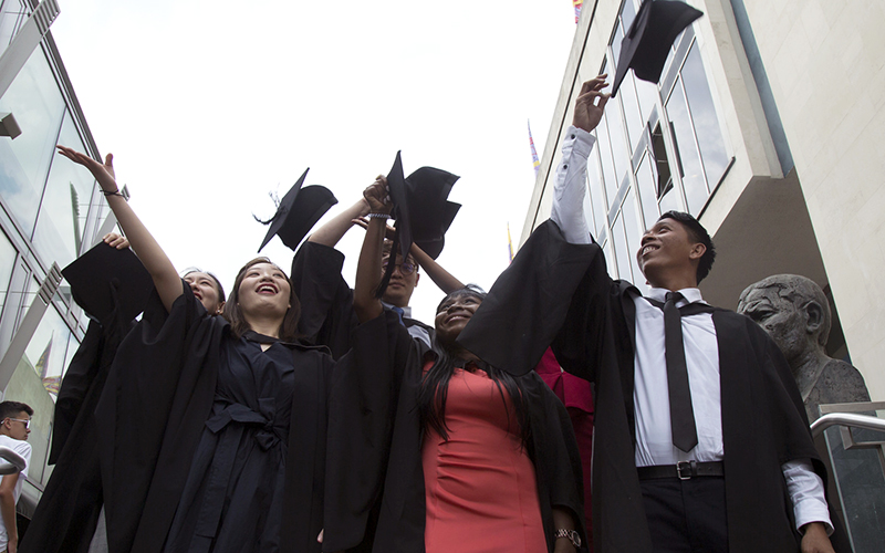 University graduates throwing mortarboards in the air