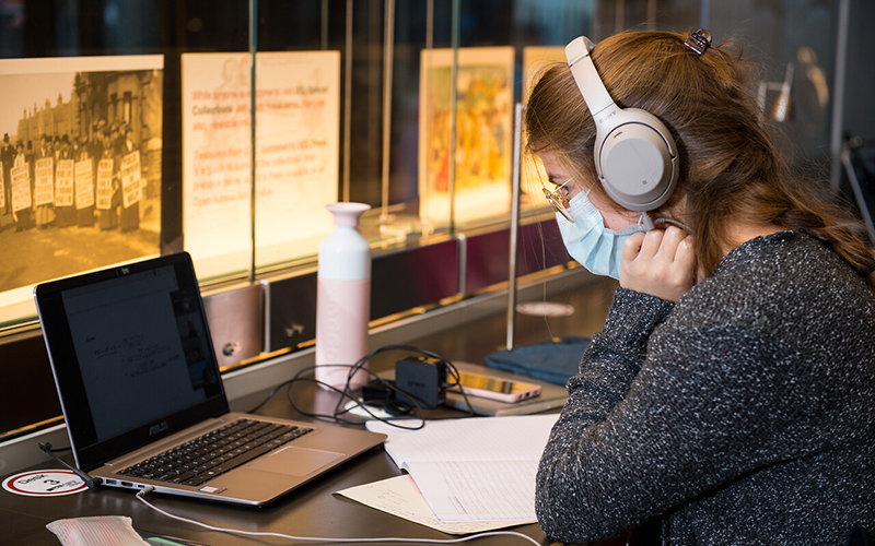 Female student studying with laptop and headphones in the UCL Student Centre