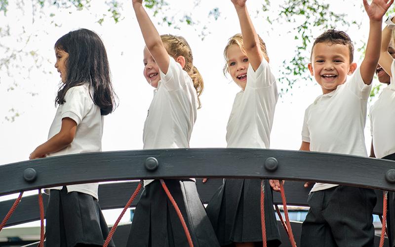 Primary school boys and girls on playground equipment