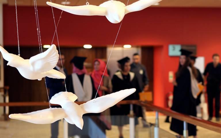 Hanging sculptures of birds in flight in front of graduating students