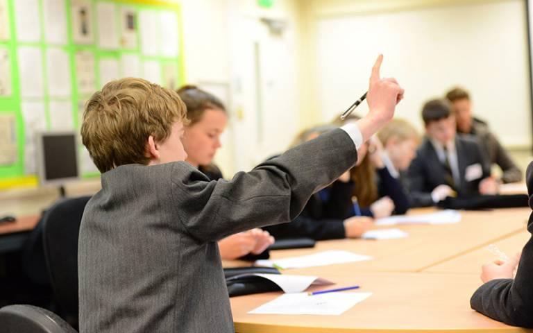 Boy in school uniform asking question