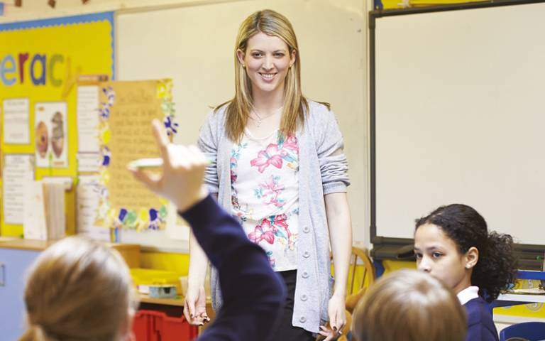 Primary school students raise hands in front of female teacher