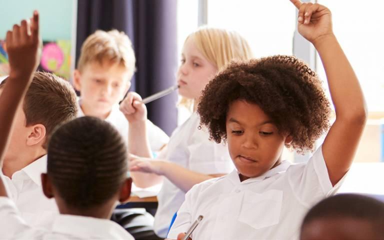 Girls raises hand in Primary school classroom