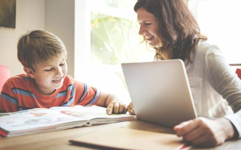 Child sitting and reading with parent. Image: Rawpixel.com via Shutterstock, courtesy of Dean Crow, CIE