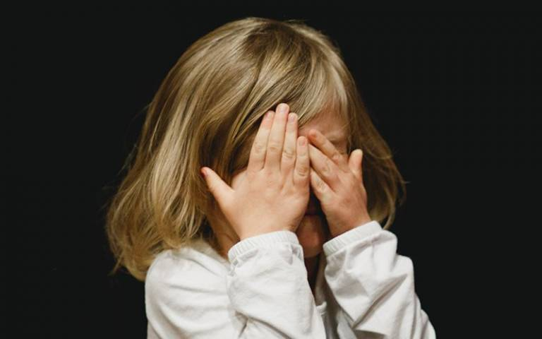 Upset child covering face with hands