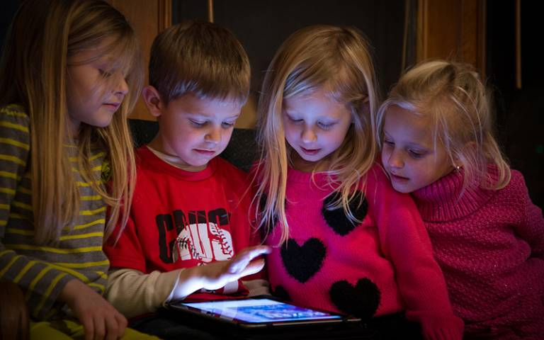 Children captivated reading a tablet