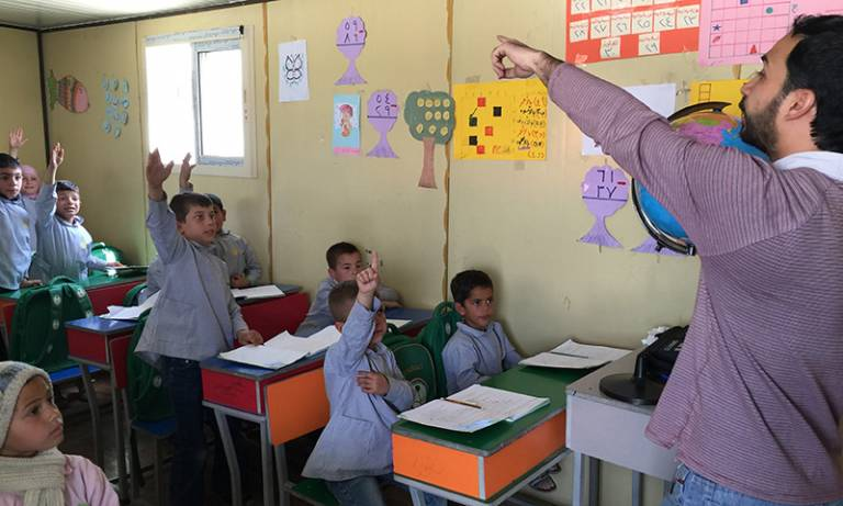 Children raising hands to answer questions in class