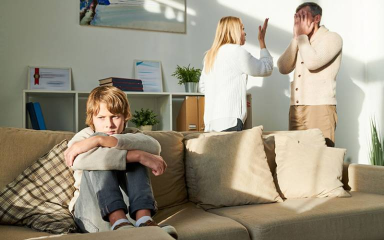 Child sat on sofa looking upset while parents argue in the background
