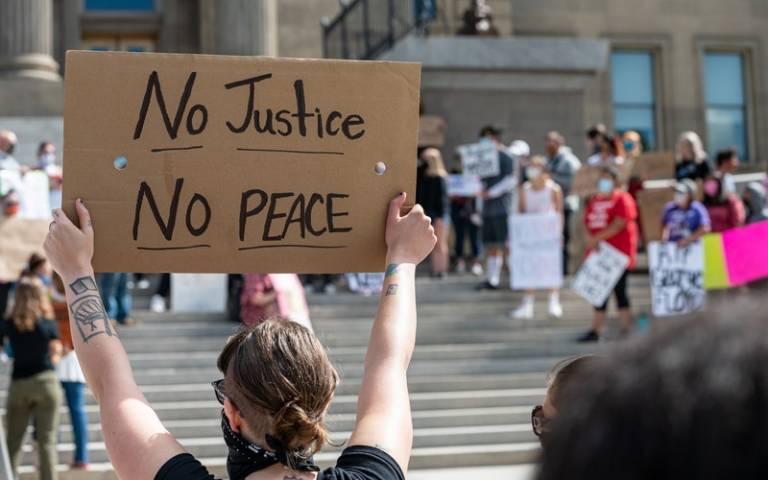 Person holding no justice, no peace sign. Image: Brett Sayles via Pexels