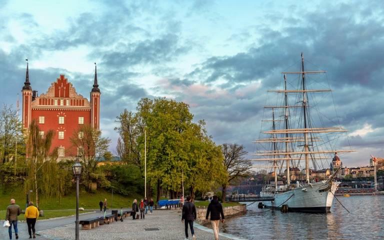 People walking near water in Sweden. Image: Vicente Viana Martínez via Pexels