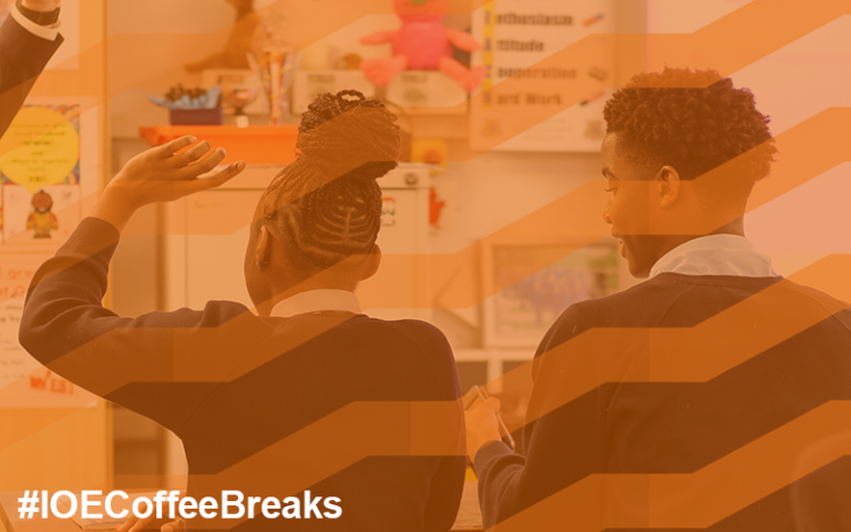 Two A Level pupils raise hands while teacher stands in class #IOECoffeeBreaks