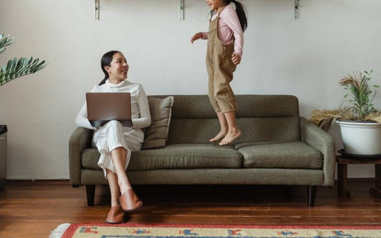 Mother sitting and daughter jumping on sofa next to her. Image: Ketut SubiyantofromPexels