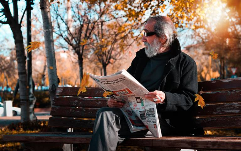 Man on a bench with newspaper