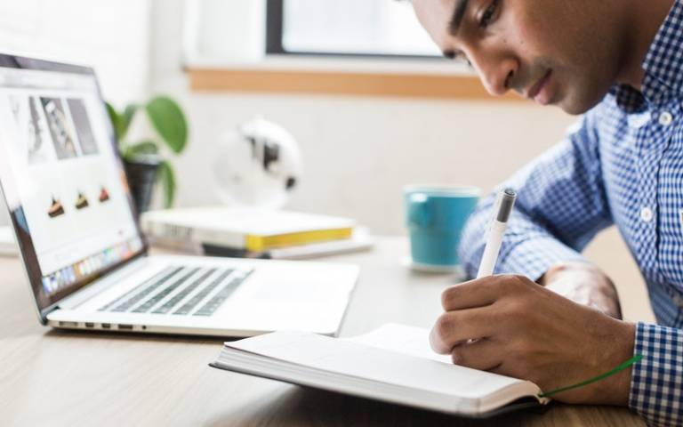 Person writing in notebook at their desk. Image: Burst via Pexels