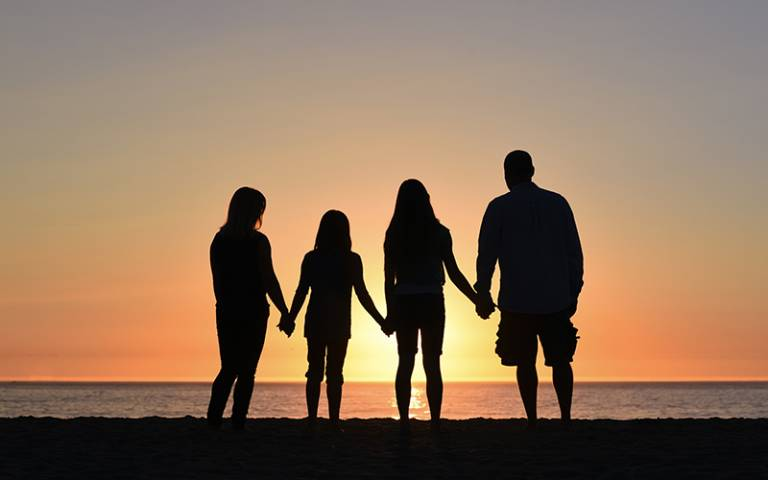 Silhouette of family on the beach. Image: Jude Beck via Unsplash