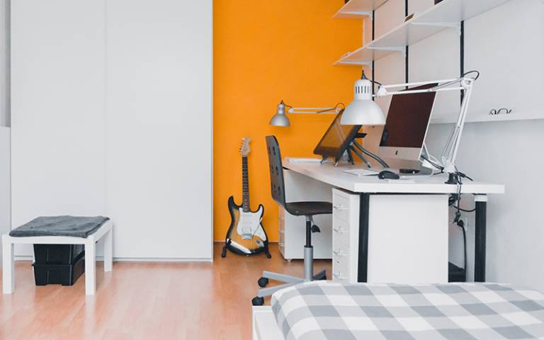 Student room with a bed, desk and computer. Image: Norbert Levajsics via Unsplash