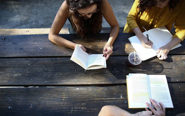 International students studying outside on wooden table. Image: Alexis Brown via Unsplash