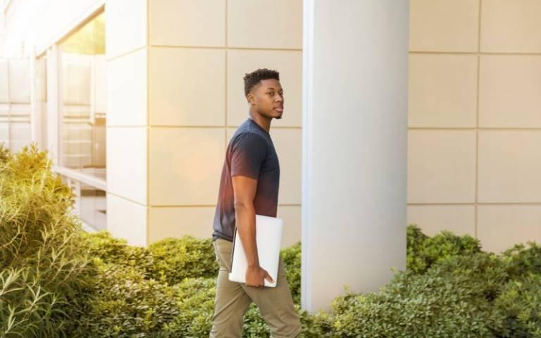 man walking into university