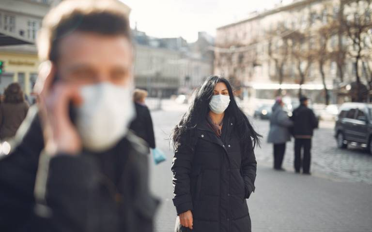 Woman standing in street with mask on. Image: Gustavo Fring via Pexels