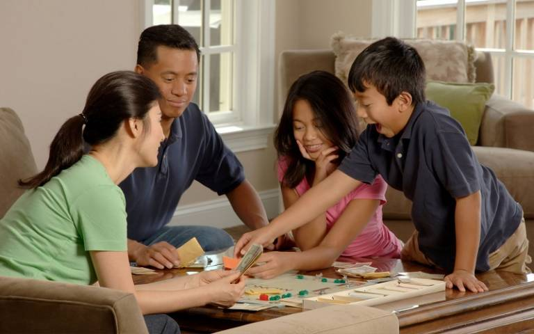 Family playing a board game sitting around a coffee table in their home. Photographer Bill Branson for National Cancer Institute via Unsplash.