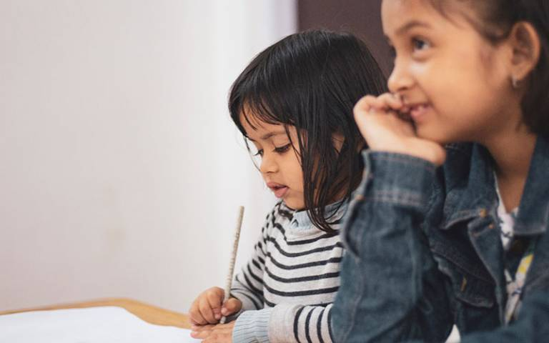 Girls writing at preschool