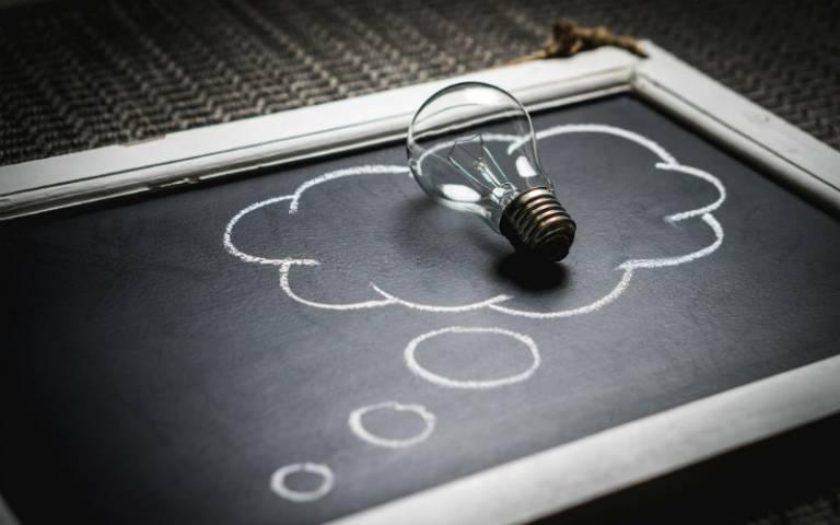 Lightbulb on blackboard with a speech bubble drawn around