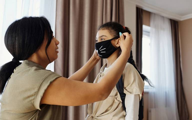Mother putting a face mask on her daughter. Photo by August de Richelieu from Pexels