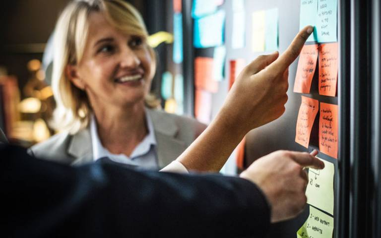 Colleagues in an office brainstorming ideas on post-it notes