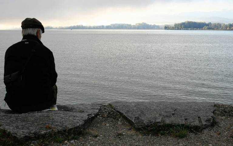 Older man sitting alone staring at a lake