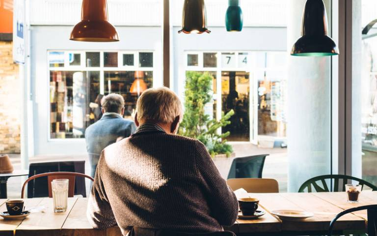Older man sitting alone in a cafe