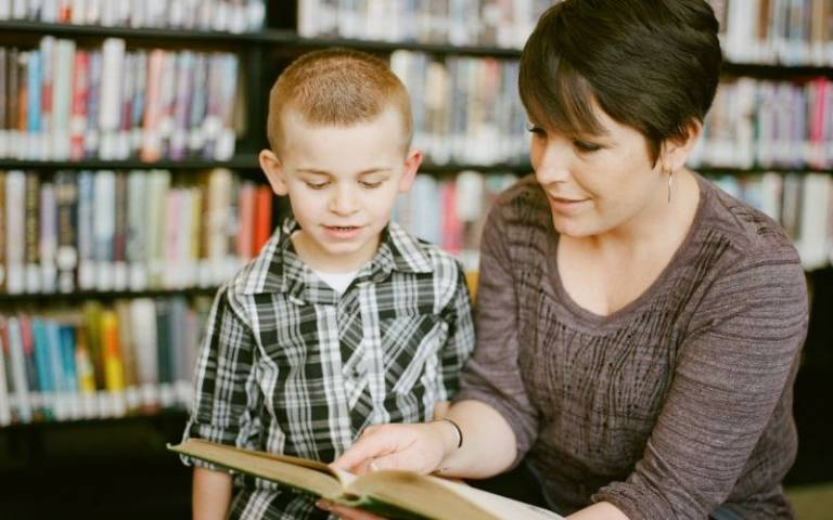 Primary teaching assistant reading with pupil. Image: Aw Creative via Unsplash