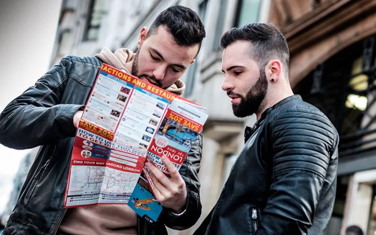 Two men reading a map aloud